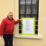 Eugene Murphy TD reads Jessamine's poem outside his office in Strokestown